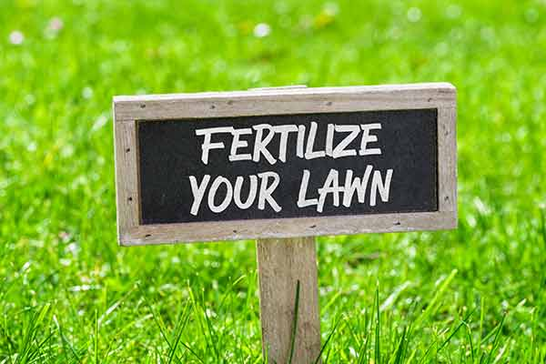 green yard with 'fertilize your yard' sign