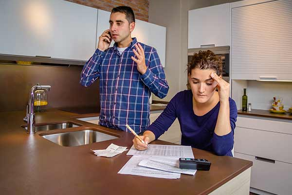 angry man on phone next to woman doing calculations
