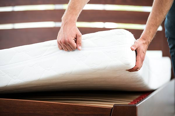 hands flipping a mattress