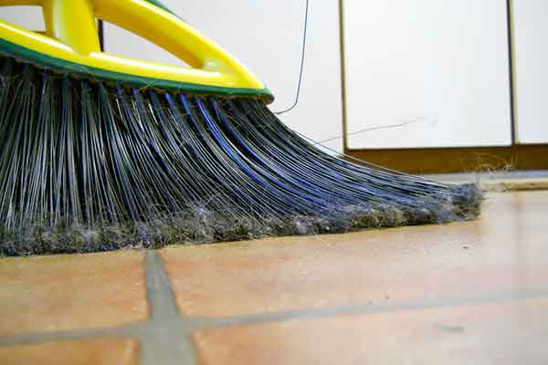 close-up of a broom sweeping tile floor