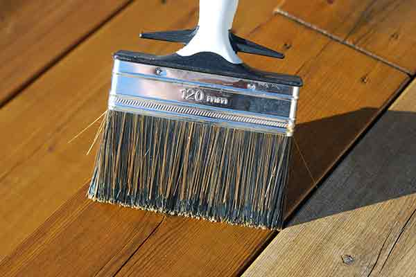 close-up of brushing stain on wooden deck
