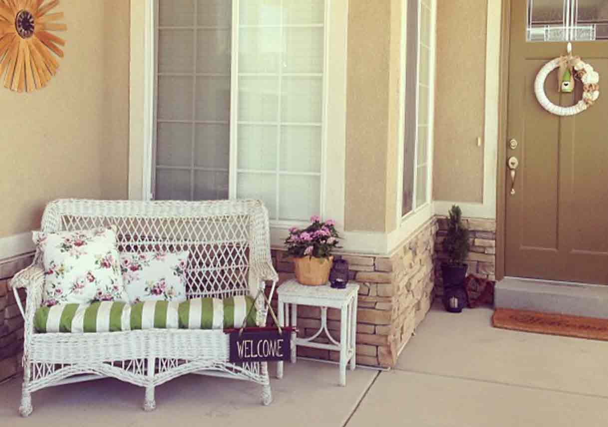 porch with white wicker furniture and colorful cushions
