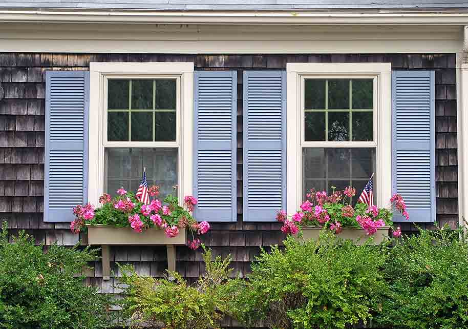 window boxes with pink flowers against blue shutters