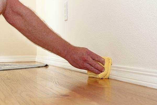hand holding a rag cleaning baseboards