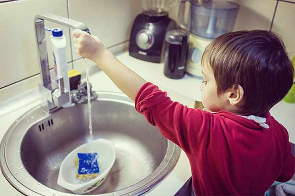 little boy washing dishes in kitchen sink