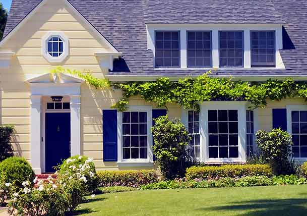 Pale yellow cottage-style home with blue door and shutters and white trim