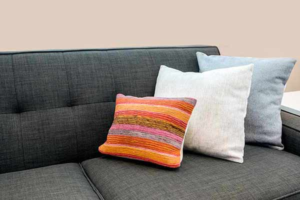 closeup of bright colored accent pillows on a black couch