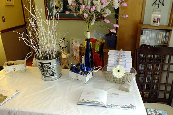 table with guest book favors and flowers