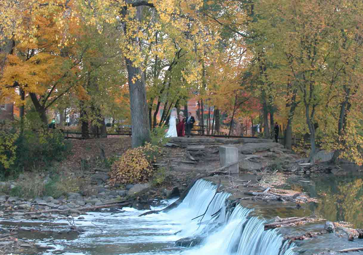 bride in the distance at an old mill