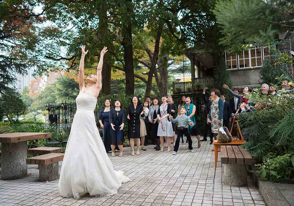 bride tosses bouquet to crowd at outdoor wedding