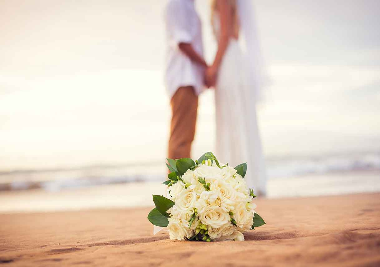 couple kissing behind wedding bouquet on the beach