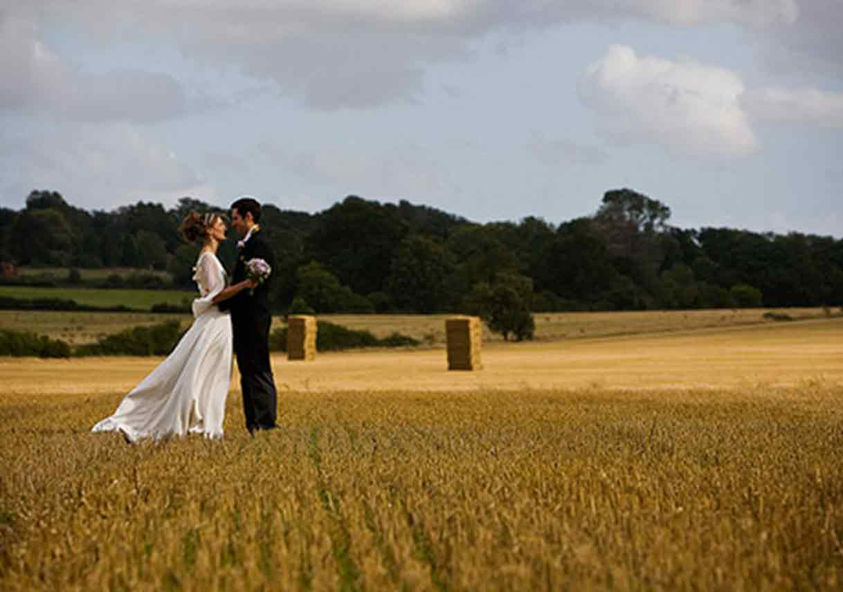 wedded couple stands in large wheat field