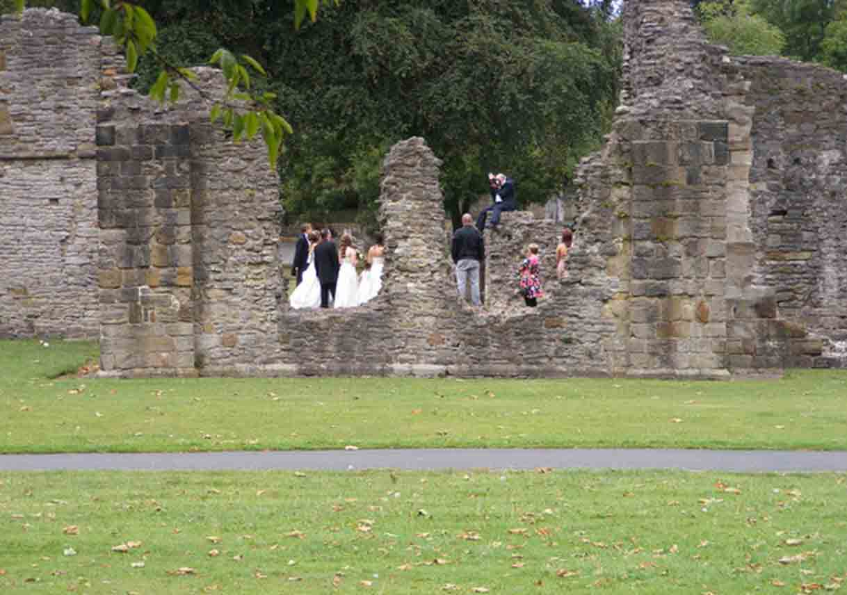 wedding party stands in center of old ruins