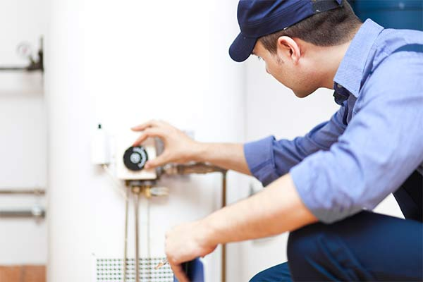 plumber turning down heat on water heater