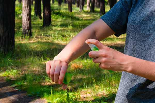 woman in forest uses spray against mosquitoes