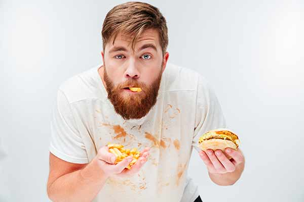 bearded man eating a messy burger