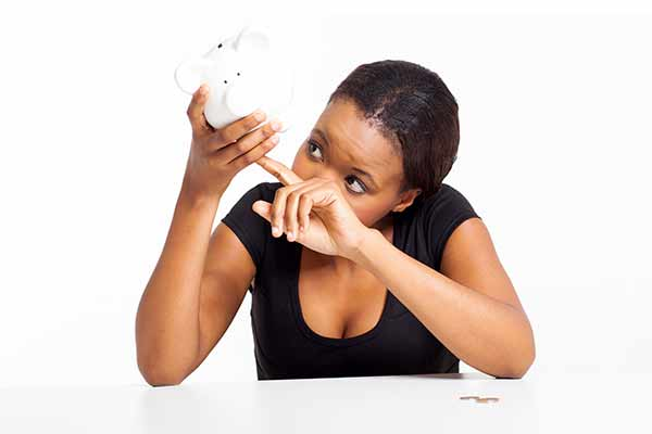 woman holding empty piggy bank