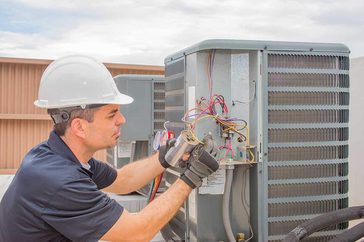 HVAC technician fixing a broken condenser