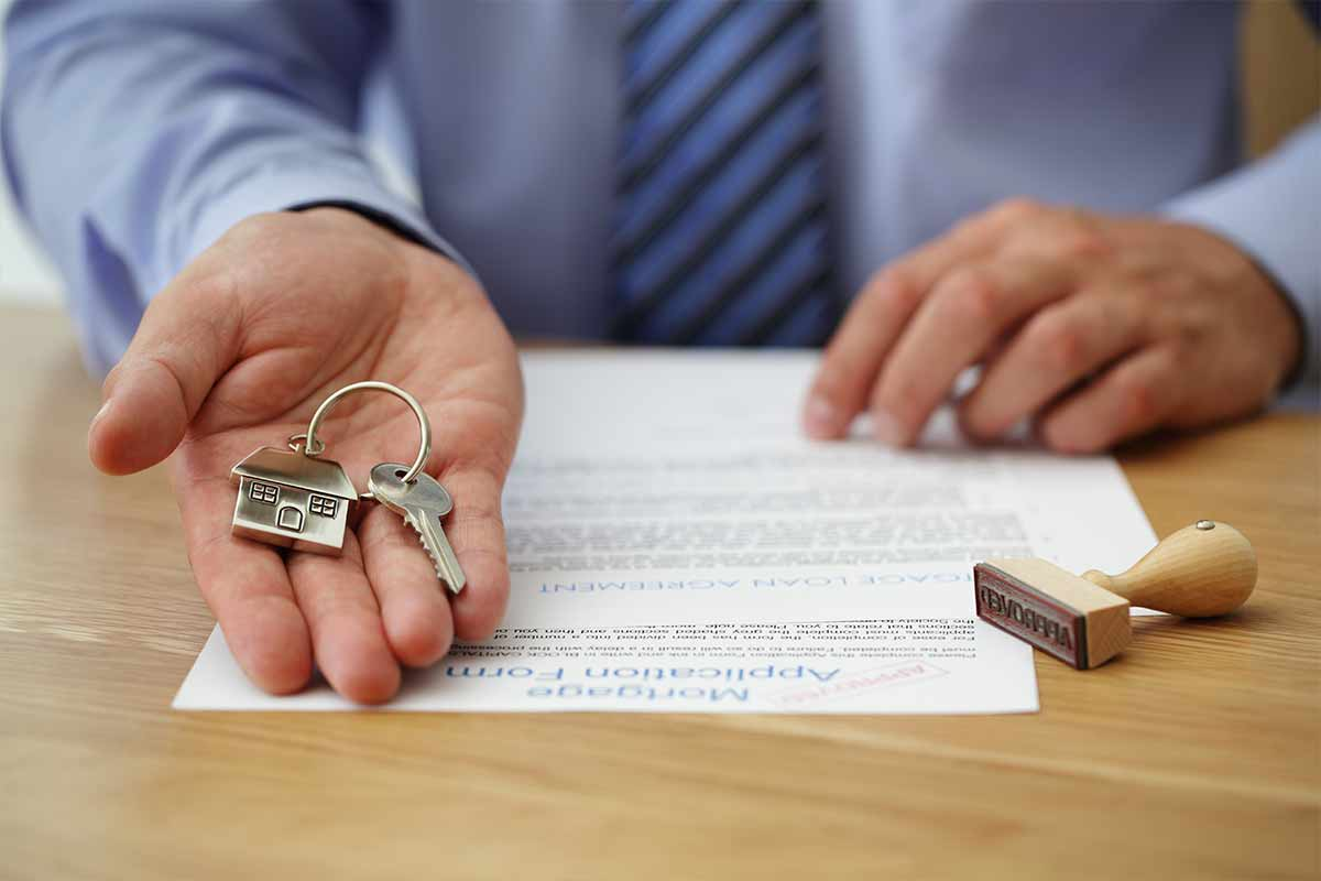 real estate agent hands over house keys