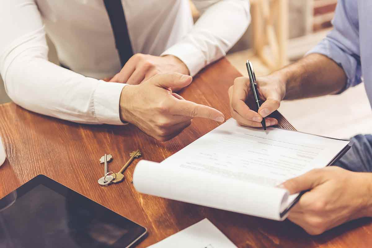 hand signing a real estate contract