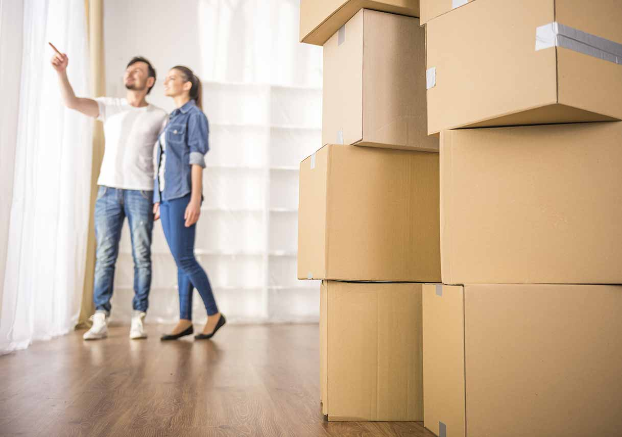 Moving boxes in bare room with couple