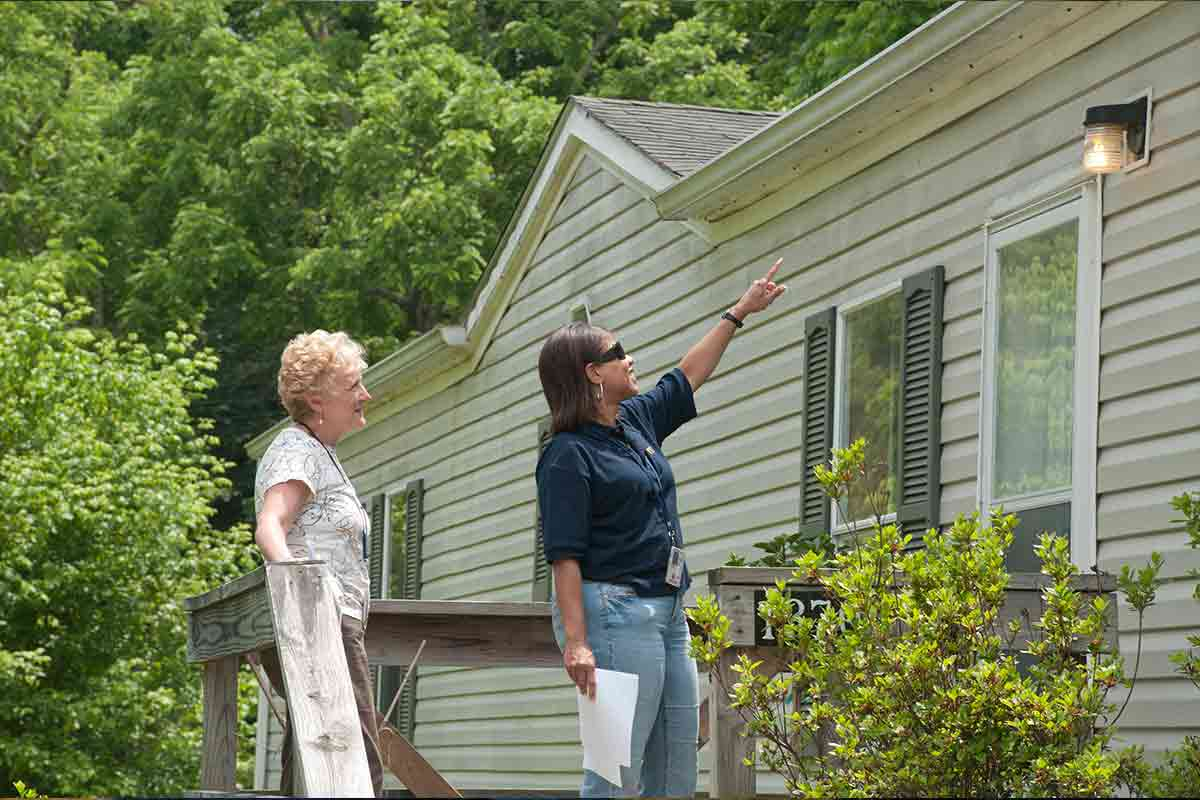 two women inspecting home's exterior vinyl siding