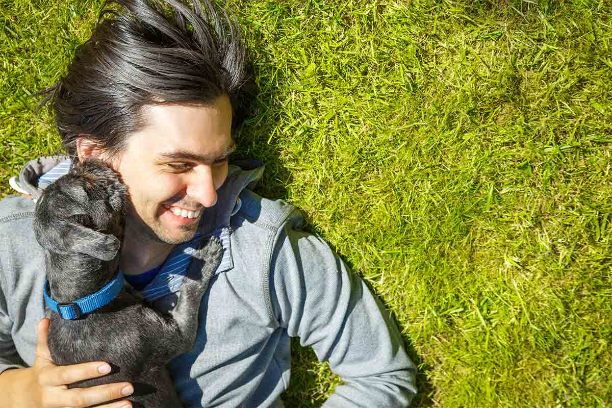 Dog licking man's face while laying in grass
