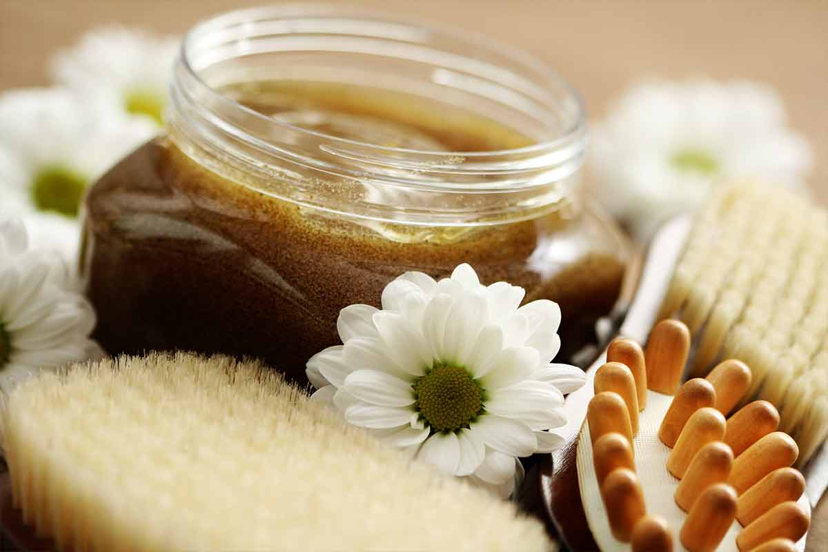 body scrub in jar surrounded by flowers and brushes