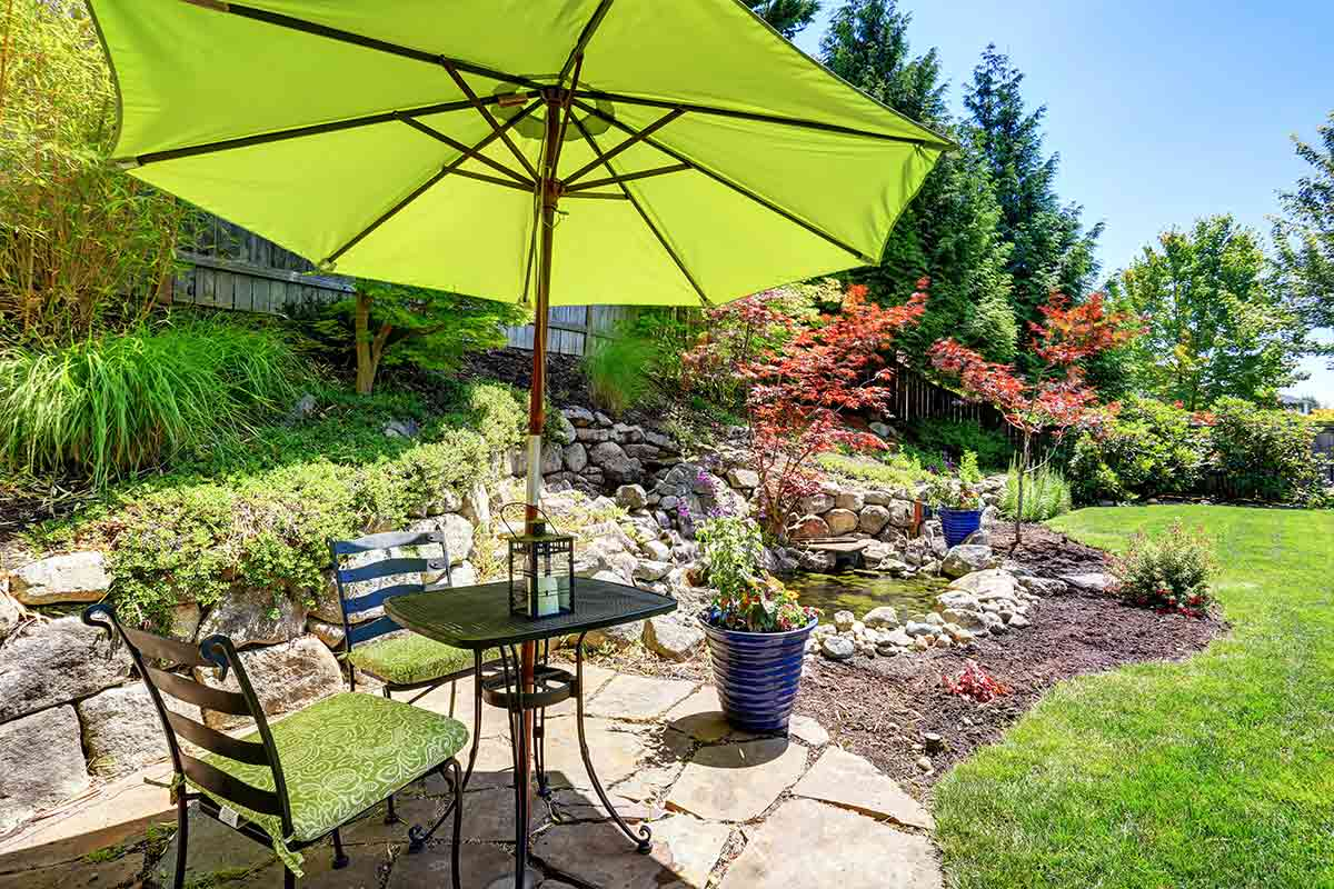 small-stone-patio-with-green-umbrella-and-small-pond