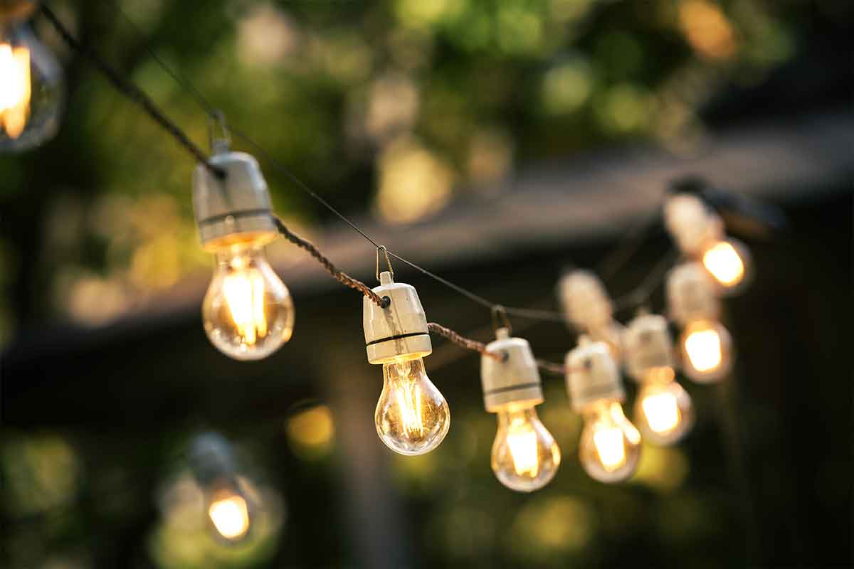 Strings of outdoor Edison-style light bulbs lighting a residential patio