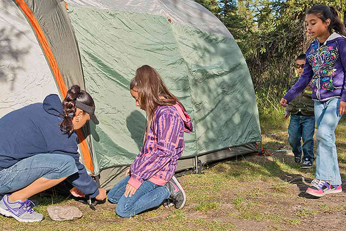 Woman setting up a tent with three children
