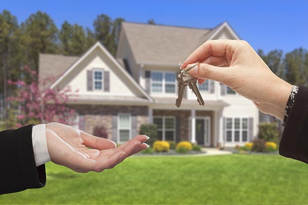 real estate agent handing over house keys in front of house