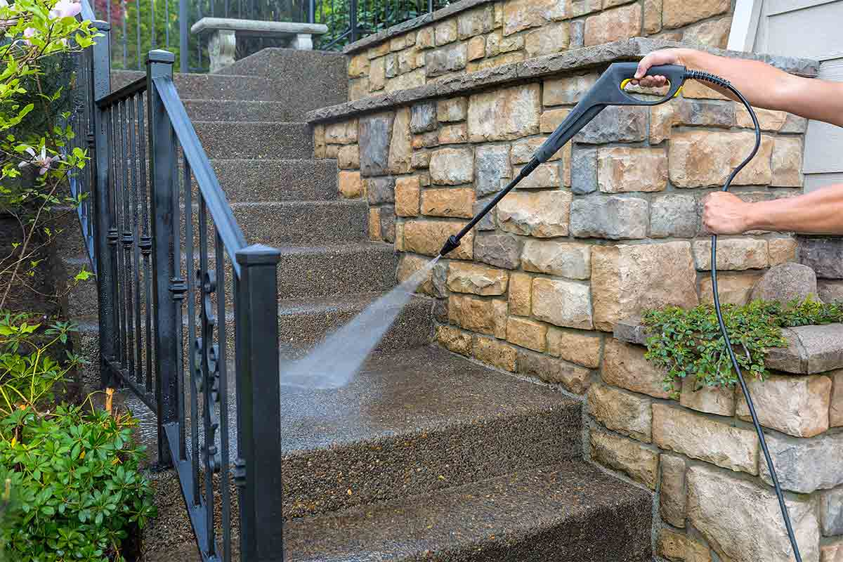 A person pressure washing a set of concrete and stone stairs