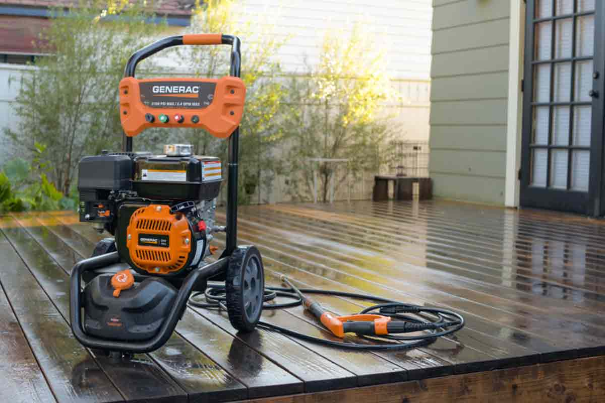 Orange and black, professional-grade gasoline pressure washer on wooden deck