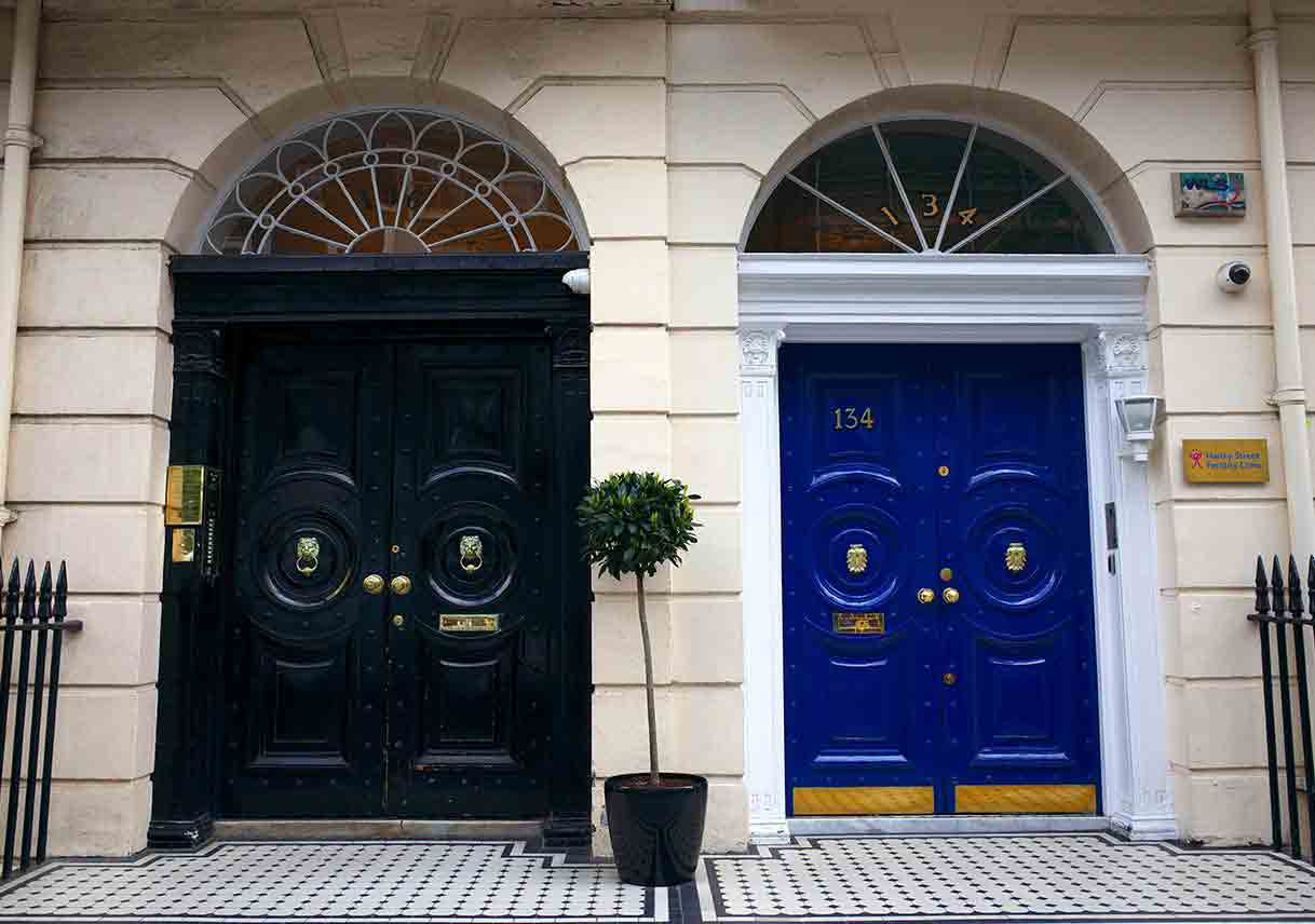 Black door with elaborate fanlight and blue door with simple fanlight