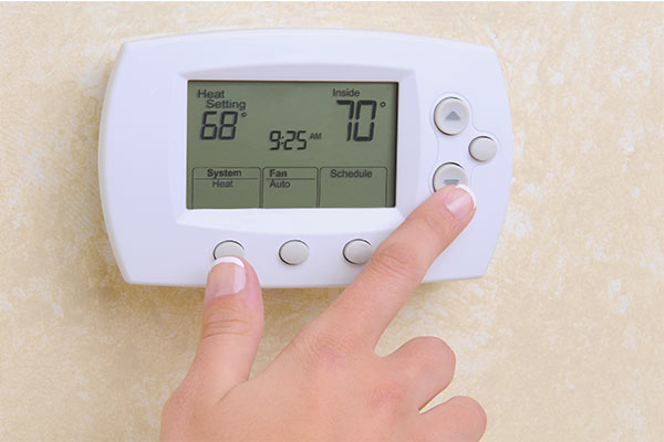 hand setting room temperature on programmable thermostat