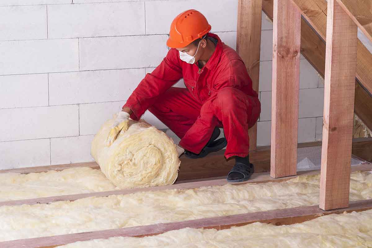 man installs fiberglass insulation in attic