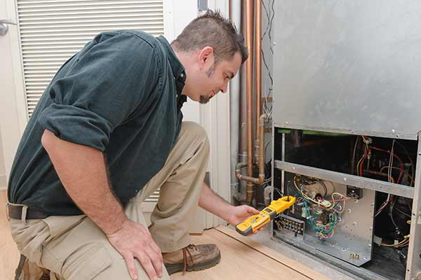 HVAC technician using a meter to check heat pump