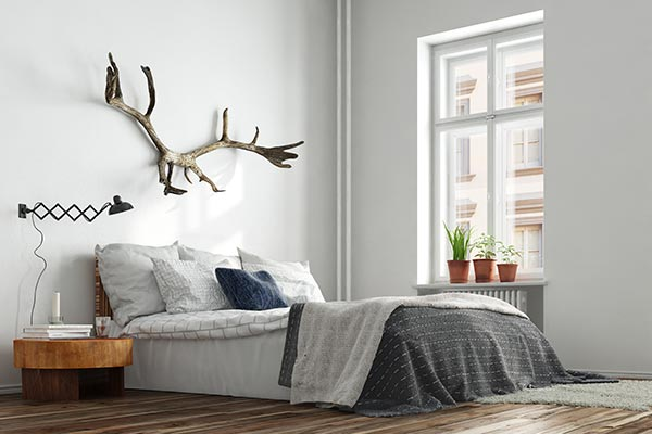 clean, modern bedroom with bed, nightstand, and antlers on wall