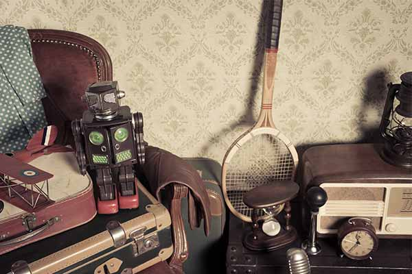 Assorted vintage items stacked in the attic with retro wallpaper background