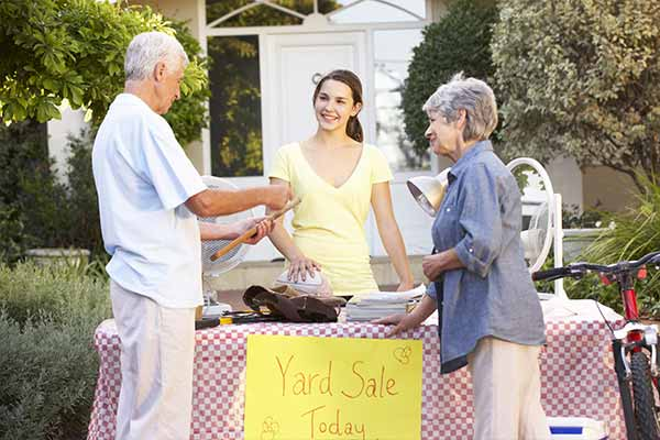 Older couple talking to Girl Holding Yard Sale
