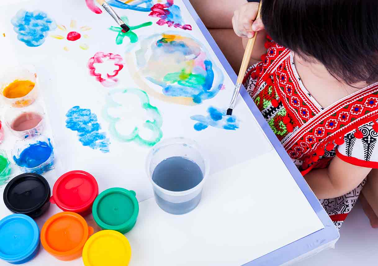 little girl using paintbrush to paint watercolor paints