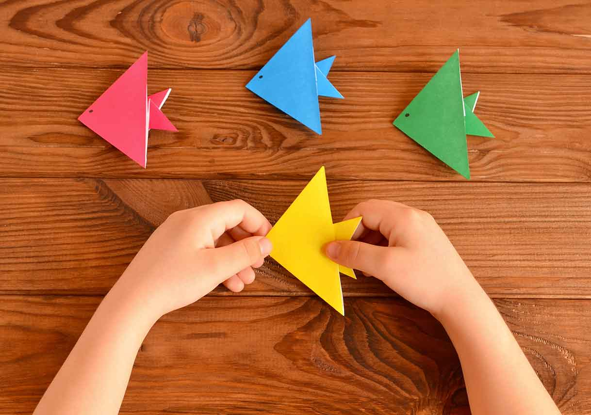 child holds origami fish