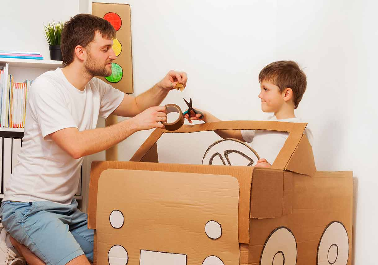dad and son building cardboard box car