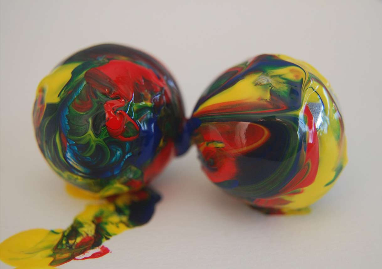 marbles covered in paint on white paper