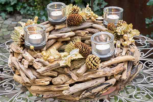 Christmas centerpiece with wood, pine cones, and four candles