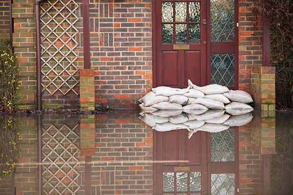 sandbags outside the front door of a flooding house