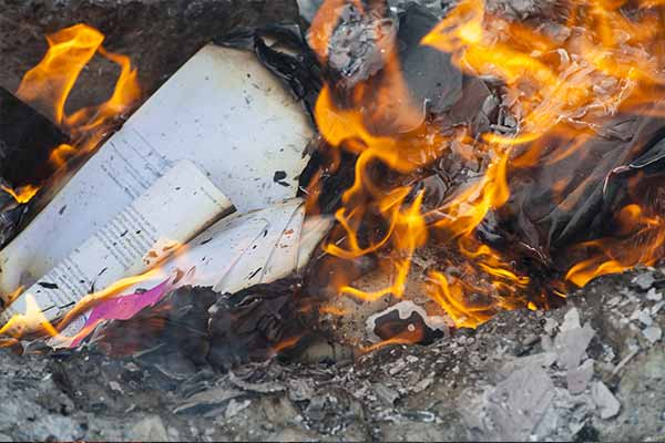 white partially burned paper among flames