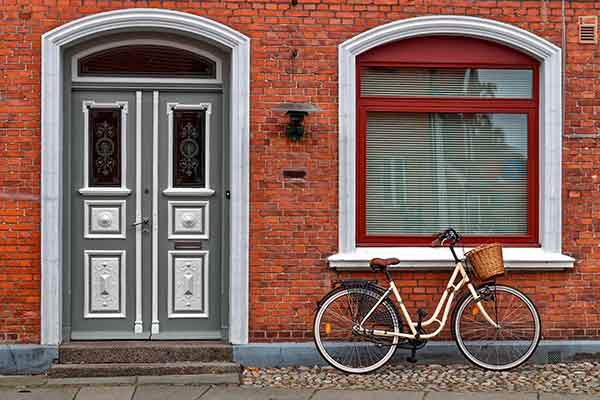 bike parked in front of brick building with grey front door with white painted accents