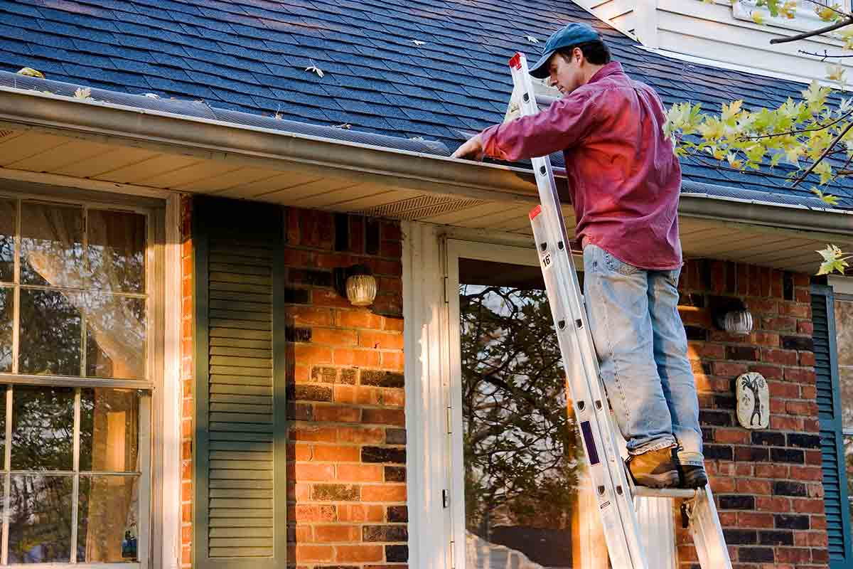 man standing on ladder while cleaning gutters
